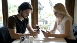 Young couple sitting at cafe table and texting messages on smartphone exchanging upset looks