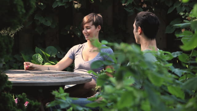 ms young couple sitting at table in garden and talking / jersey city, new jersey, usa - vegetable garden stock videos and b-roll footage