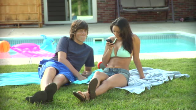 MS, Young couple sitting beside pool, looking at mobile phone, Middlesex, New Jersey, USA