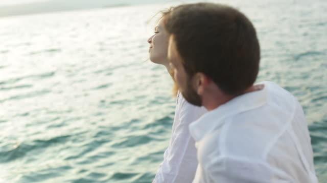 cu young couple sitting by the sea sharing a kiss. - ブラック島点の映像素材/bロール