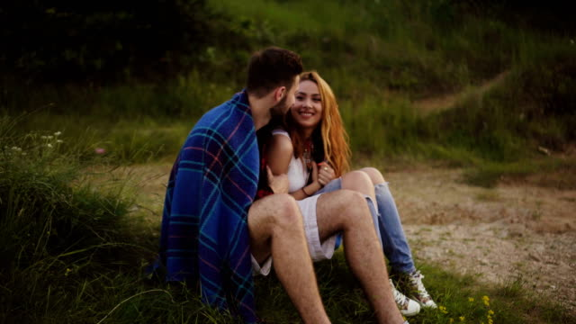Junges Paar sitzt umarmt auf dem Rasen