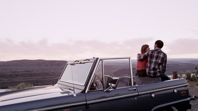 ms young couple sitting in convertible off road vehicle kissing - convertible stock videos & royalty-free footage