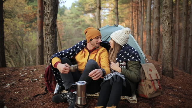 young couple sitting in front of tent and kissing on beautiful autumn day - camping stock videos & royalty-free footage