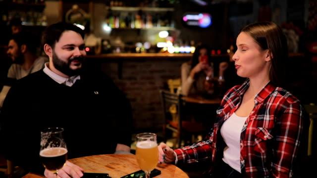 vidéos et rushes de jeune couple assis dans la pub - flirter