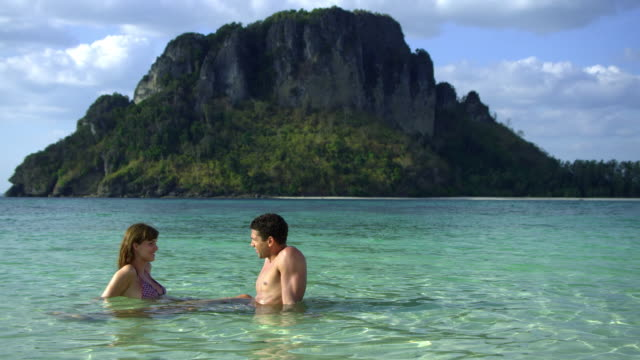 ws young couple sitting in shallow water on tropical beach, krabi, thailand - see other clips from this shoot 1459 stock videos and b-roll footage