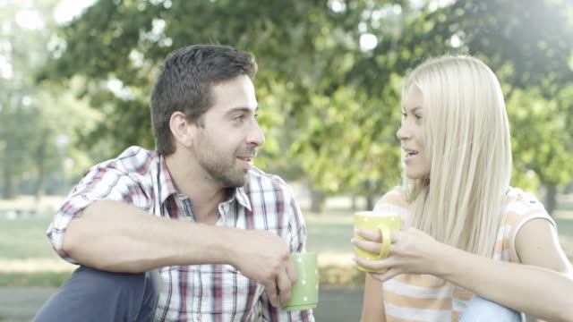 Young couple sitting in the park and drinking coffee
