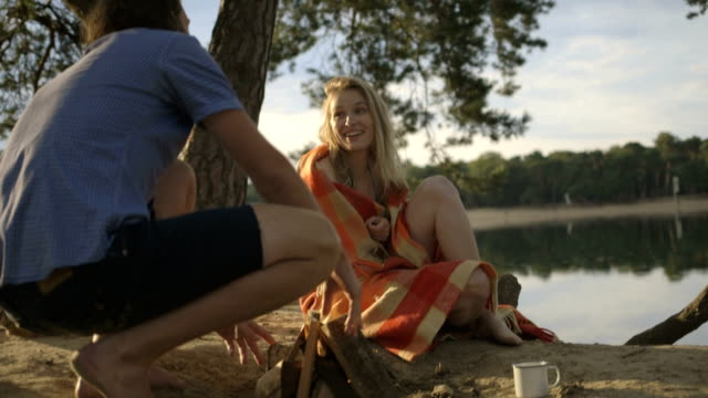 young couple sitting near campfire on riverbank - lagerfeuer stock-videos und b-roll-filmmaterial
