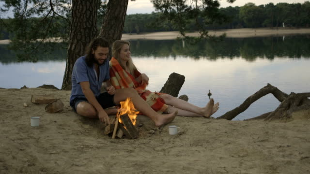Young couple sitting near campfire on riverbank