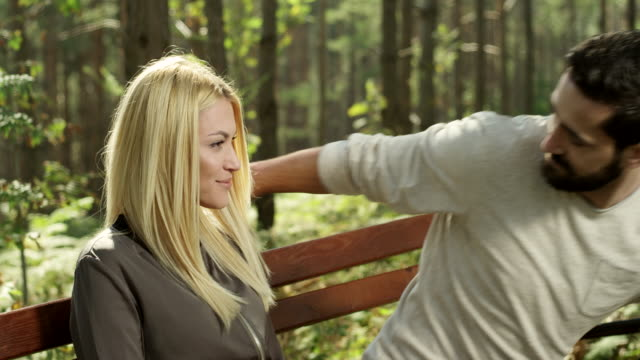 young couple sitting on a bench - bench stock videos & royalty-free footage