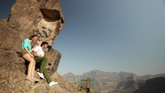 young couple sitting on a rock  - indian ethnicity stock videos & royalty-free footage