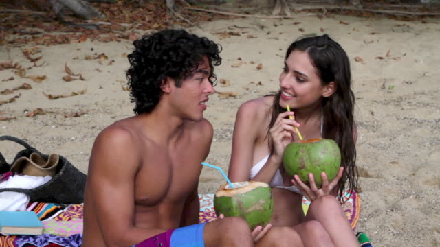 young couple sitting on beach drinking coconut milk - プエルトリコ人点の映像素材/bロール