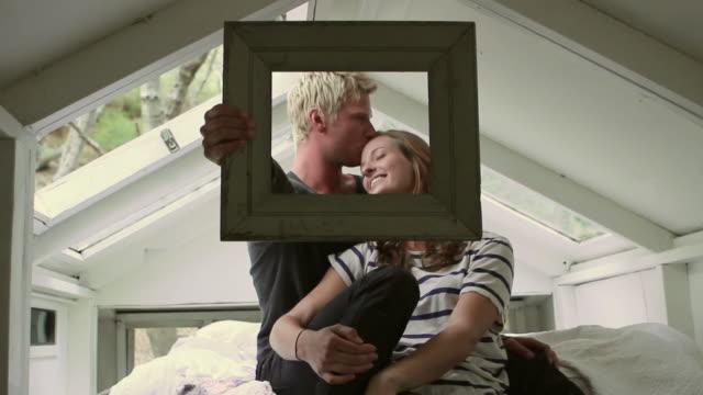 vídeos de stock, filmes e b-roll de ms young couple sitting on bed holding picture frame in front of them / big sur, california, usa - moldura de quadro composição