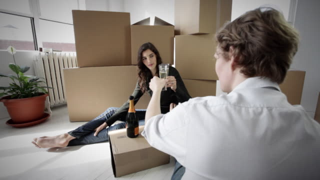 ms young couple sitting on floor of their new apartment toasting with champagne / new york city, new york, usa - bricolage video stock e b–roll
