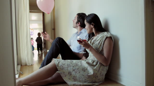 ms young couple sitting on floor relaxing and enjoying drink together, children entering with carrying balloons / santa monica, ca, united states    - young family stock videos & royalty-free footage