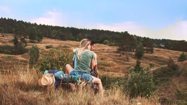 vídeos de stock, filmes e b-roll de pares novos que sentam-se no prado durante férias - casal jovem