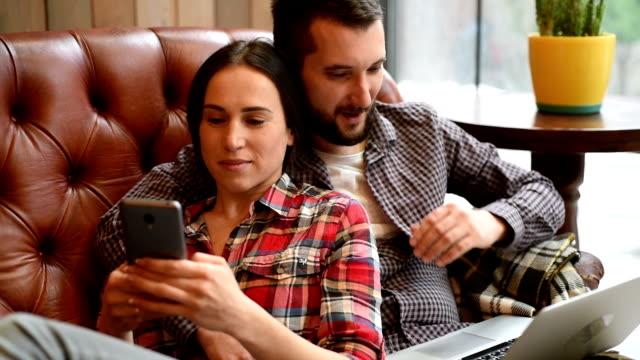 Junges Paar sitzt auf Sofa mit Zubehör