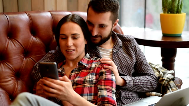 young couple sitting on sofa and using gadgets