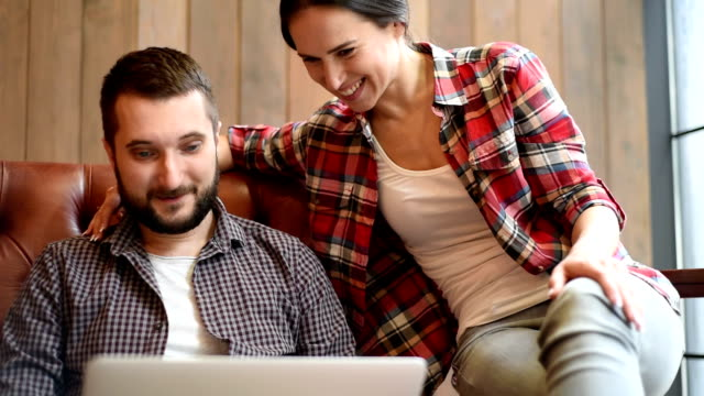 young couple sitting on sofa and using laptop