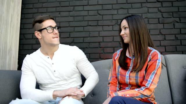 vídeos y material grabado en eventos de stock de pareja joven sentado en un sofá, conversar y sonriendo - camisa a cuadros
