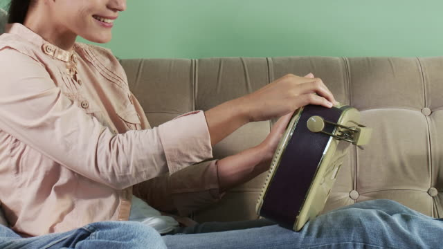 young couple sitting on sofa with radio and book - radio stock videos and b-roll footage