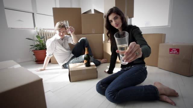 WS Young couple sitting on the floor of their new apartment with champagne / New York City, New York, USA