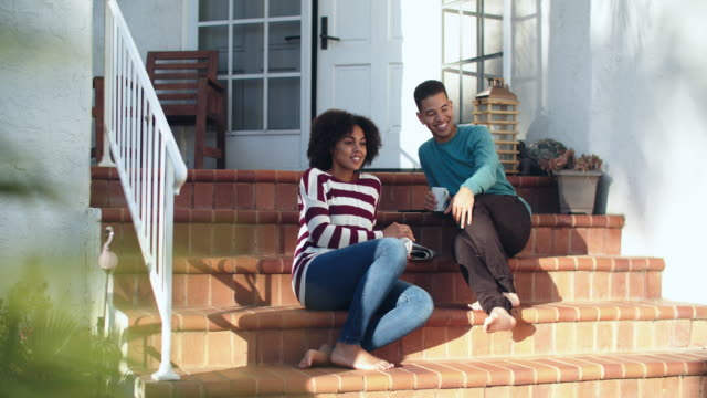 young couple sitting on the front steps of their house - in front of stock videos & royalty-free footage