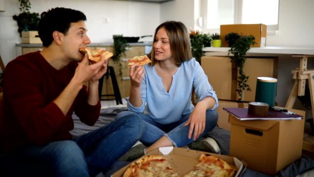 junges paar sitzt auf der matratze mit pizza zum abendessen - moving down stock-videos und b-roll-filmmaterial
