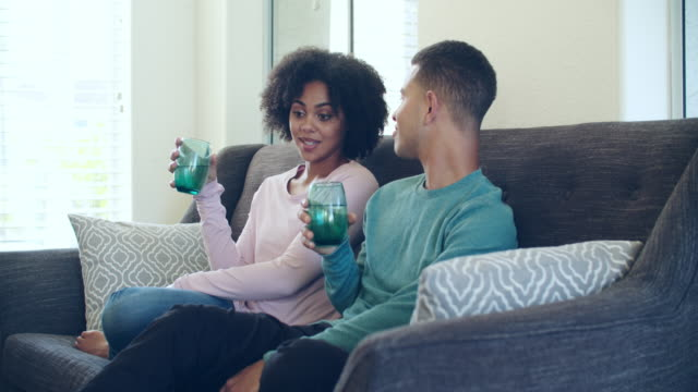 young couple sitting on the sofa talking - young couple stock videos & royalty-free footage