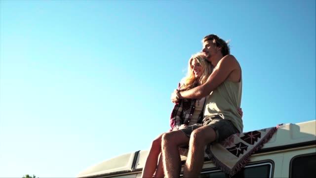 junges ehepaar sitzt am sonnigen tag auf dem dach des van - junges paar stock-videos und b-roll-filmmaterial