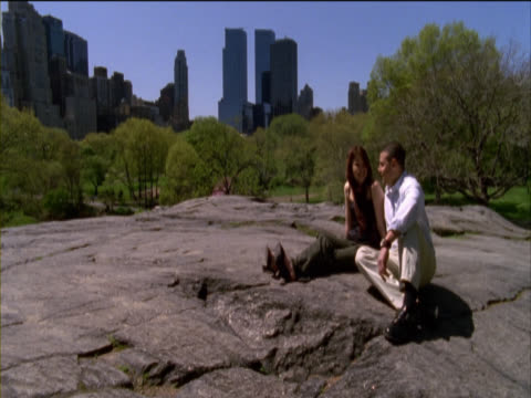 young couple sitting side by side on a rock and talking in central park, new york, usa - side by side stock videos & royalty-free footage
