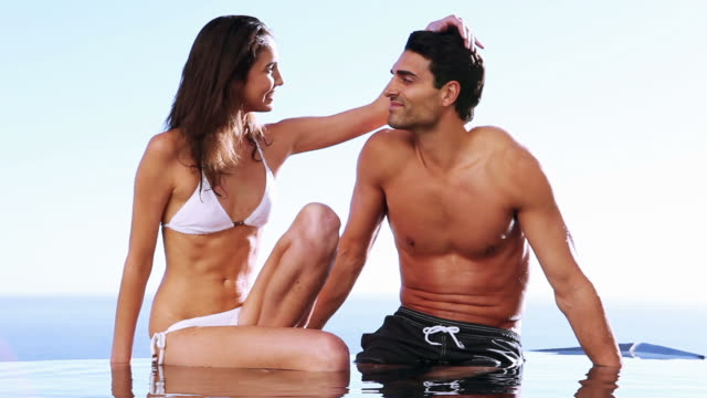 couple sitting together on the edge of a swimming pool - halbbekleidet stock-videos und b-roll-filmmaterial