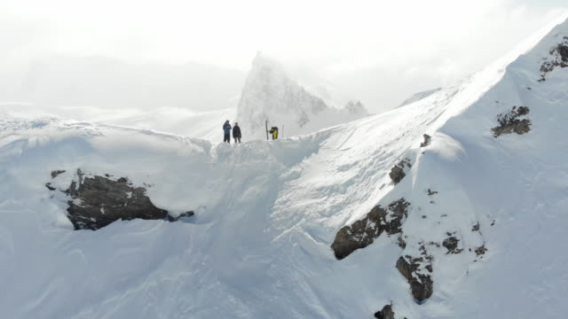 young couple skiing mountain climbing extreme off piste