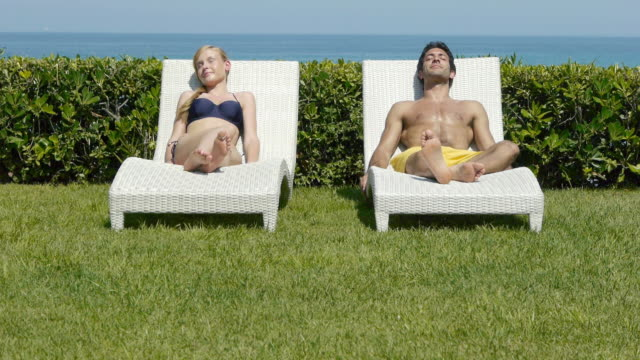 young couple sleeping on sun loungers - beach chairs stock videos & royalty-free footage