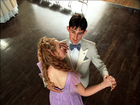 young couple slow dance together in circle round the dance floor - schleife stock-videos und b-roll-filmmaterial