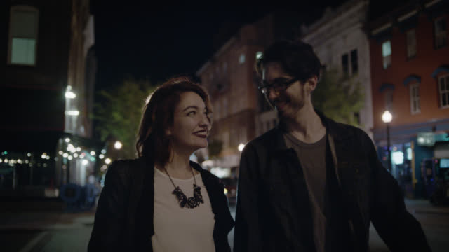 MS SLO MO. Young couple smile at each other as they cross city street at night.