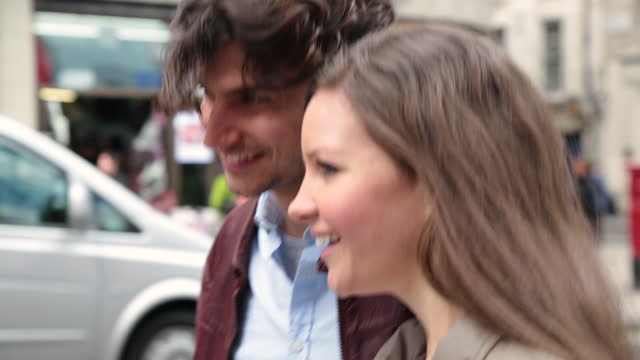 Young couple smile at each other as they stroll through London on a sunny day.