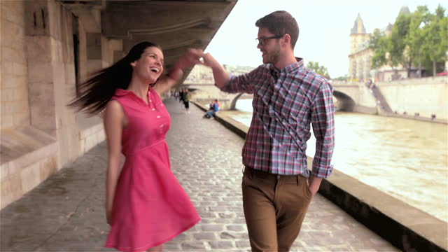 young couple smile at each other as they walk and twirl along the river seine on sunny day in paris. - モーターボート点の映像素材/bロール