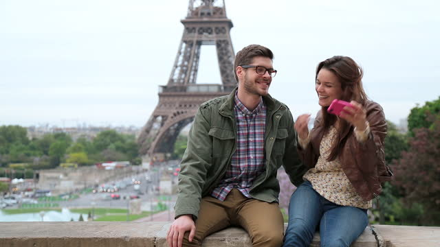 vidéos et rushes de young couple smile for a smartphone selfie with eiffel tower in background. - tour eiffel