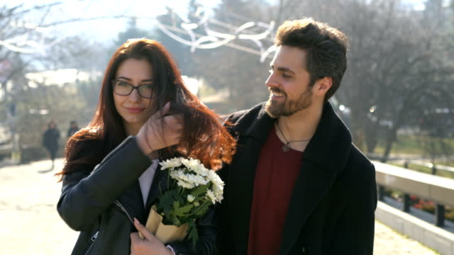 Young couple smiling at camera with flowers bouquet and flirting.