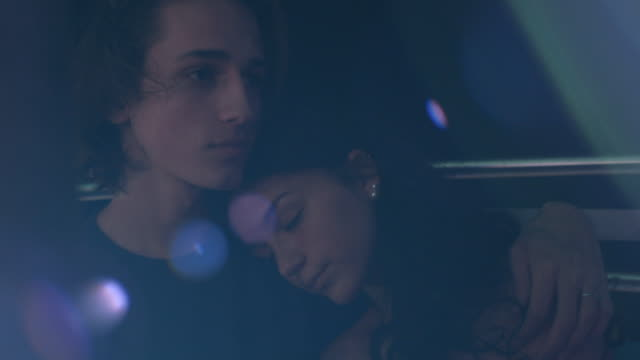 a young couple snuggles on a ferris wheel at a carnival - neon stock videos & royalty-free footage