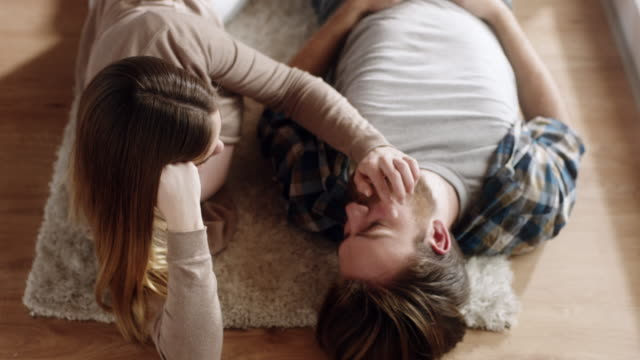 young couple spending romantic time together on the floor at living room - guardare verso il basso video stock e b–roll