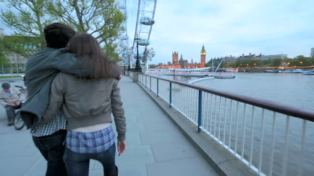 young couple spin into each other‰ûªs arms as they stroll down the south bank in london. - millennium wheel stock videos & royalty-free footage