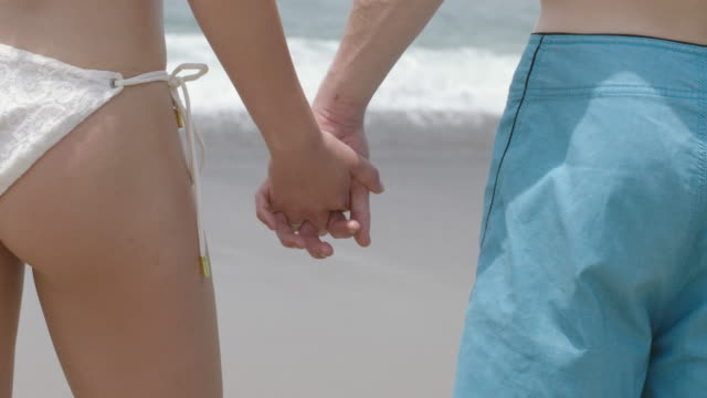 stockvideo's en b-roll-footage met young couple stand holding hands in front of the pacific ocean 4k - zwembroek