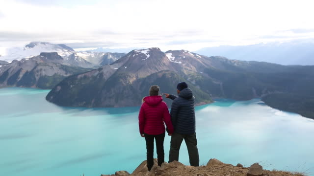 young couple stand on a mountain top and admire the view - mountain peak stock videos and b-roll footage