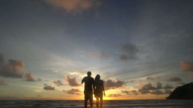 young couple standing by the ocean in yellow sunset - looking away stock videos & royalty-free footage