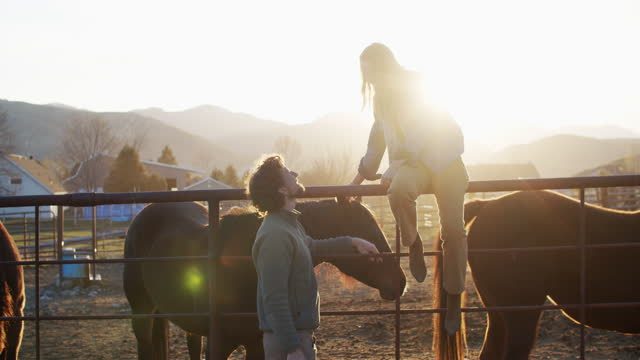 young couple standing by their horses talking - romance stock videos & royalty-free footage