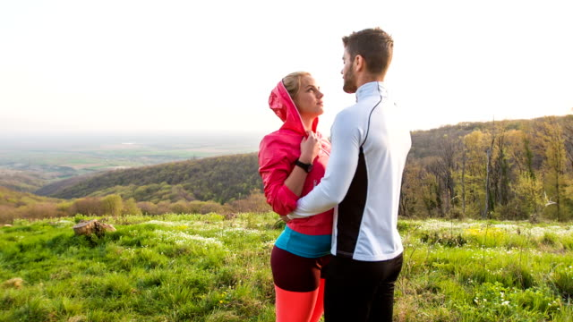Young couple standing face to face in nature, taking a break after jogging