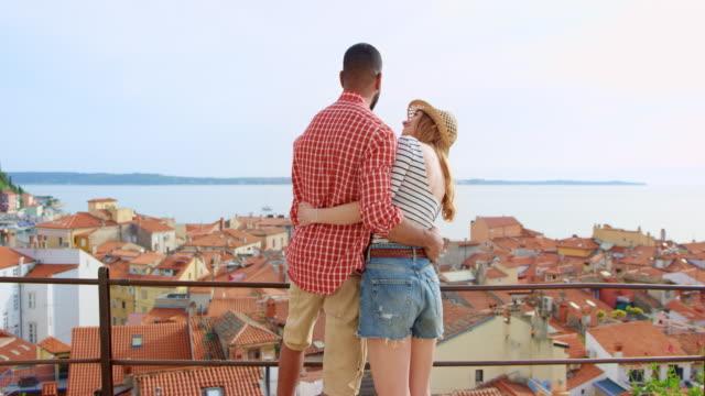 vídeos de stock, filmes e b-roll de jovem casal de pé sobre uma passarela acima uma cidade costeira e apreciando a vista - casal jovem