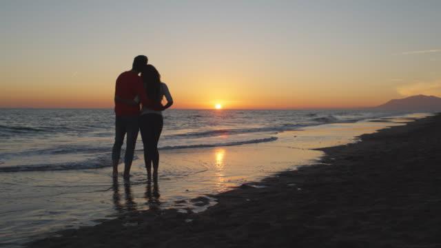 young couple standing on beach in sunset - 輪郭点の映像素材/bロール