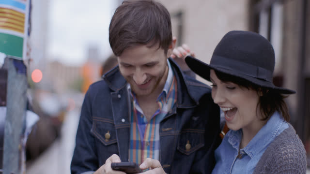 Young couple standing on street corner text friends and laugh
